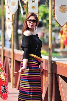 W średnim wieku tajlandzka dama w kolorowym północnym tajlandzkim stylowym kostiumu przy plenerowym turystycznym miejscem w chiang mai lanna tajlandia