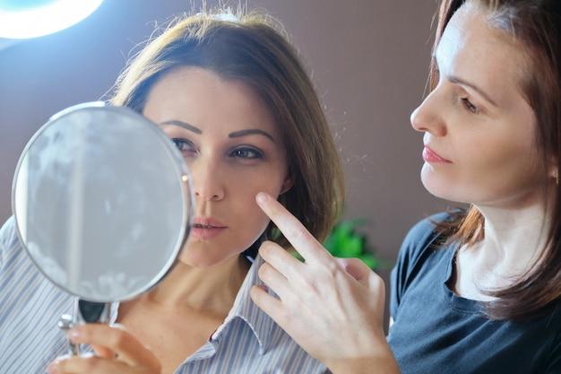 W średnim wieku żeński pacjent patrzeje w lustrze i żeńska kosmetyczka pokazuje na twarzy