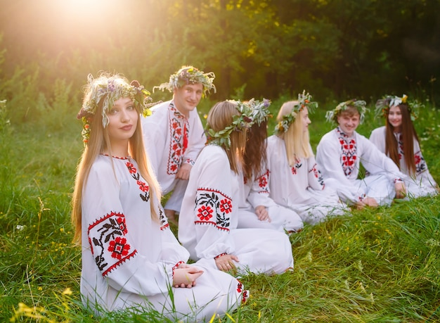 W środku lata grupa młodych ludzi o słowiańskim wyglądzie siedzi przy ognisku.