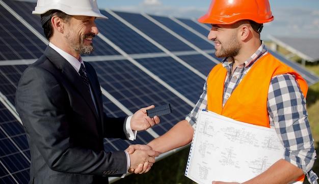 W stacji solarnej klient biznesowy i brygadzista ściskając ręce.