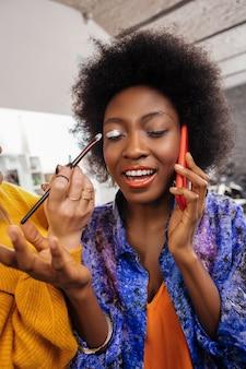 W studio mody. młoda stylistka w żółtym grubym swetrze pracuje z modelką podczas nakładania srebrnych cieni na powieki