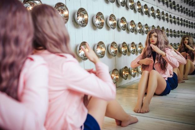 W studiu siedzi syntetyczna dziewczyna glamour, sztuczna lalka o pustym wyglądzie i długie liliowe włosy.