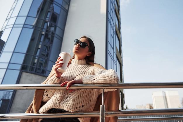 W sweter z dzianiny. młoda piękna dziewczyna w ciepłych ubraniach spaceruje po mieście w weekendy