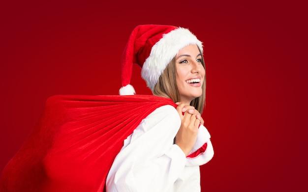 W święta bożego narodzenia młoda blondynka podnosi torbę pełną prezentów
