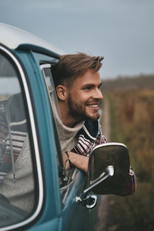 W szczerym polu. przystojny młody mężczyzna wychyla się przez okno furgonetki i uśmiecha się, siedząc na przednim siedzeniu pasażera