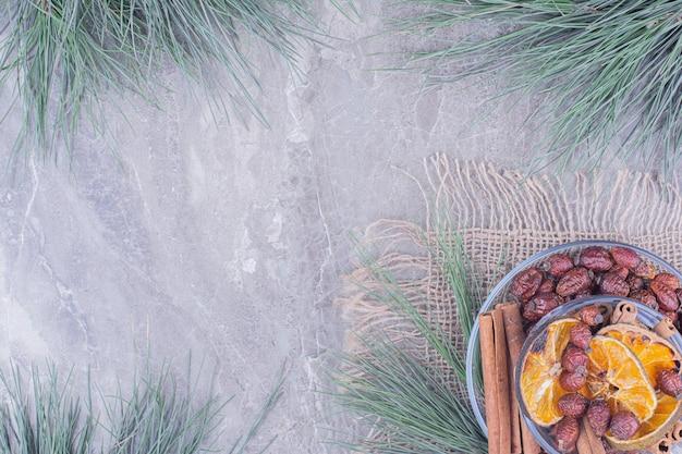W szklanej filiżance osusz plastry pomarańczy i biodra z cynamonem