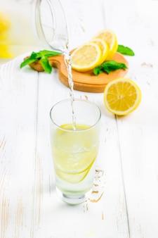 W szklanej zlewce zimna lemoniada nalewa dzbanek na białym drewnianym tle otoczonym cytrynami.
