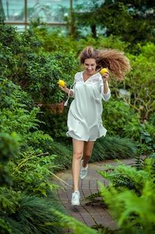W szklarni. kobieta w białej sukni z cytryną w rękach