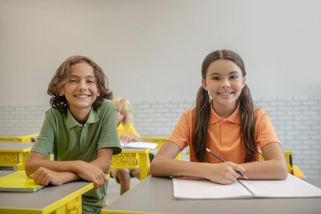 W szkole. dwóch uczniów siedzi przy biurku i wygląda na szczęśliwych