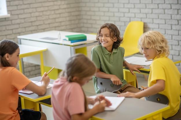 W szkole. dzieci siedzą przy ławkach w klasie i wyglądają na zadowolone
