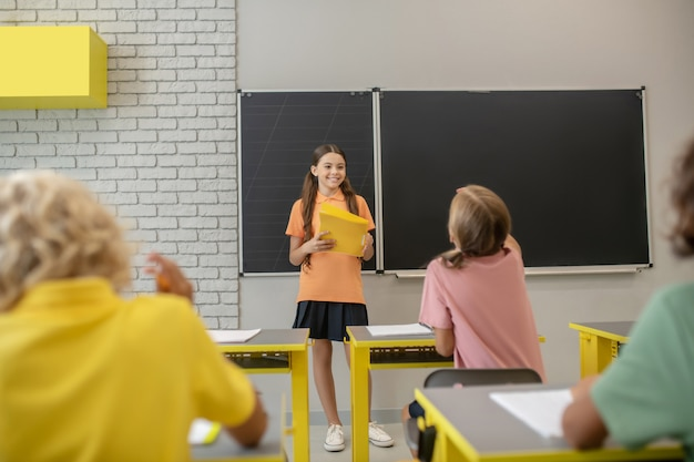 W szkole. dziewczyna w pomarańczowej koszuli stojącej przy tablicy