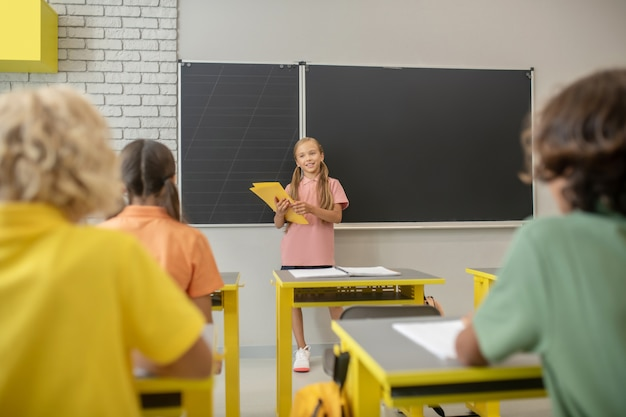 W szkole. dziewczyna w różowej koszulce stojącej przy tablicy