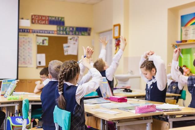 W szkole i uczniach dziecko podniosło rękę, aby odpowiedzieć nauczycielowi, przyjaźni