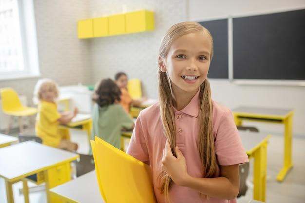W szkole. śliczna uczennica w różowej koszulce ładnie się uśmiecha
