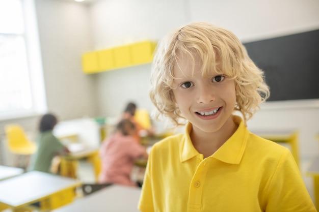 W szkole. śliczny uczeń w żółtej koszulce ładnie się uśmiecha