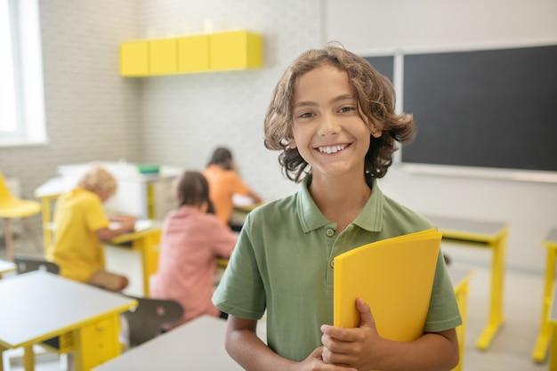 W szkole. słodki uczeń w zielonej koszulce ładnie się uśmiecha