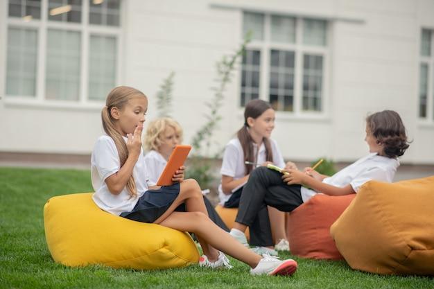 W szkole. uczniowie siedzą na torbach w pobliżu budynku szkoły