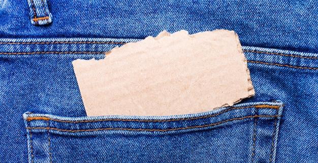 W tylnej kieszeni dżinsów znajduje się brązowa karta z miejscem na tekst.
