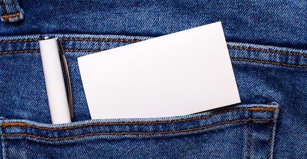 W tylnej kieszeni niebieskich dżinsów znajduje się biały długopis i biała pusta kartka z miejscem na wpisanie tekstu.