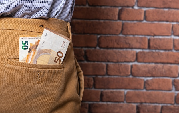 W tylnej kieszeni spodni jest dużo banknotów.