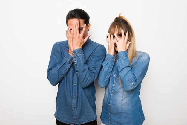 W walentynki młoda para w okularach obejmujących oczy za ręce i patrząc przez palce