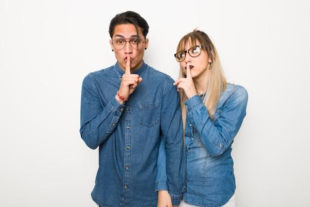 W walentynki młoda para w okularach wykazujące gestu znak milczenia oddanie palec w ustach
