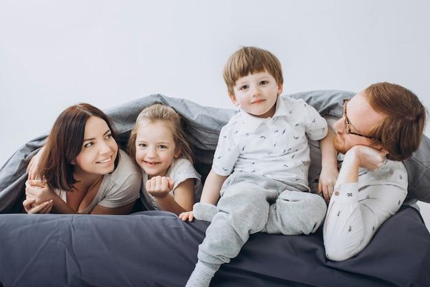 W weekendy młodzi rodzice z dziećmi bawią się w łóżku.