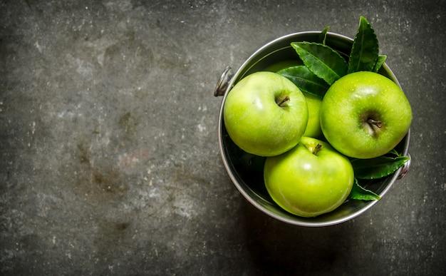 W wiadrze świeże zielone jabłka. na rustykalnym tle kamienia. wolne miejsce na tekst. widok z góry