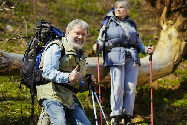 W wieku para rodziny mężczyzny i kobiety w strój turystyczny spaceru na zielonym trawniku