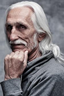 W wieku siwy kaukaski emerytowany mężczyzna myśli o życiu.