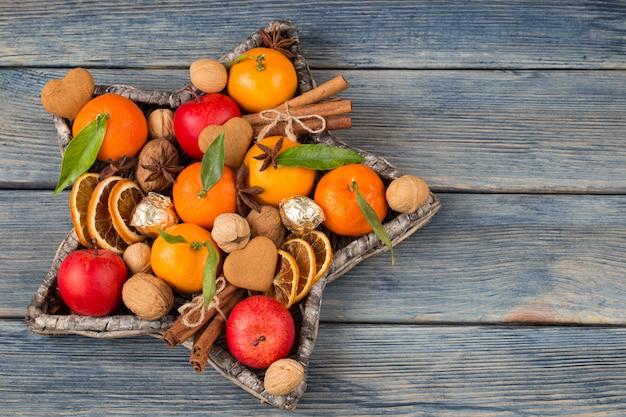 W wiklinowym wazonie w kształcie gwiazdy: mandarynki, jabłka, orzechy włoskie, cynamon, plasterki pomarańczy