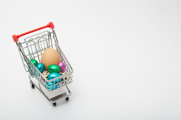W wózku spożywczym na białym tle znajdują się jajka o różnych kolorach i rozmiarach