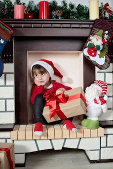 W zaimprowizowanym kominku siedzi dziecko przebrane za świętego mikołaja z pudełkiem prezentowym