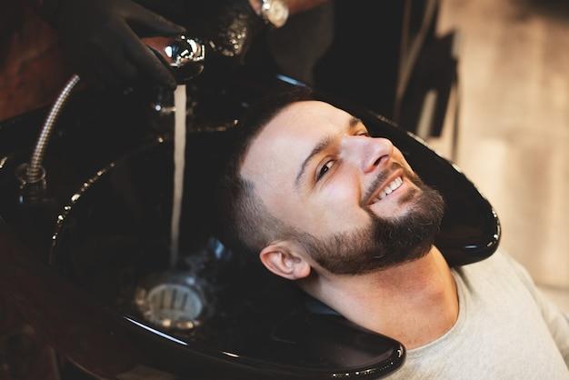 W zakładzie fryzjerskim mężczyzna myje włosy. fryzjer myje swojego klienta. po strzyżeniu umyj włosy i brody. higieny osobistej.