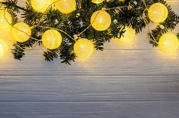 W zestawie girlanda w postaci dużych kuleczek z cienkich nitek z żółtym światłem na gałązkach świerku z miejscem na kopię na białym tle. pojęcie ciepła, komfortu, wakacji.