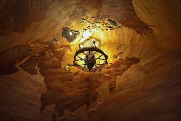 W zestawie okrągły żyrandol z żarówkami świec na tle drewnianego sufitu