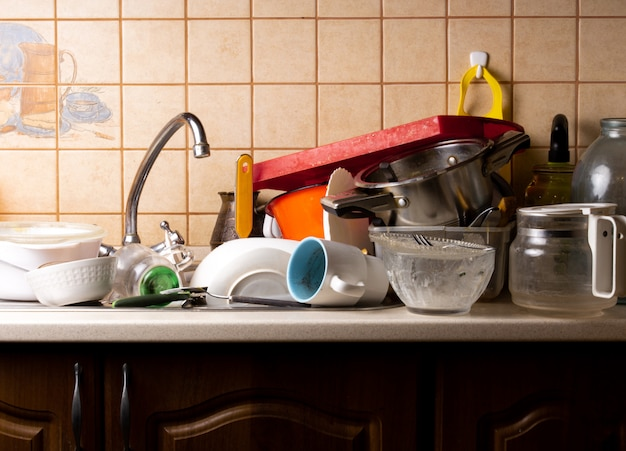 W zlewie w kuchni leży dużo brudnych naczyń, które należy umyć.