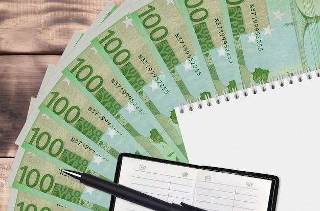 Wachlarz banknotów euro i notatnik z książką kontaktową i czarnym długopisem