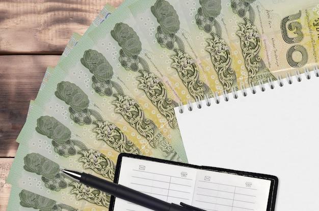 Wachlarz banknotów tajskich i notatnik z książką kontaktową