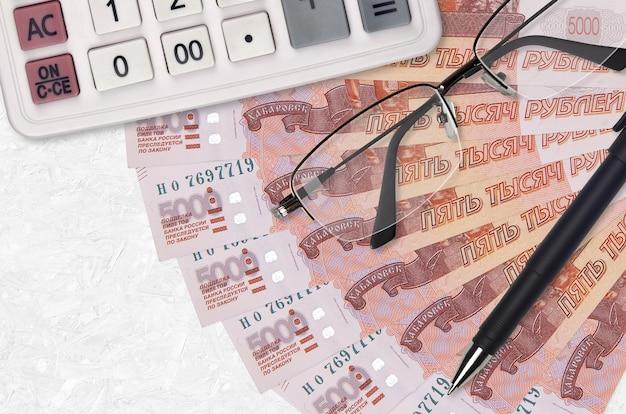 Wachlarz i kalkulator rachunków za 5000 rubli rosyjskich, okulary i długopis. kredyt biznesowy lub koncepcja sezonu płatności podatku. planowanie finansowe