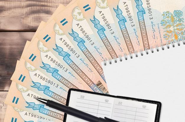 Wachlarz na banknoty 200 ukraińskich hrywien i notatnik z książką kontaktową i czarnym długopisem