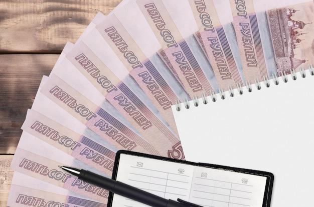 Wachlarz rachunków w rublach rosyjskich i notatnik z książką kontaktową i czarnym długopisem