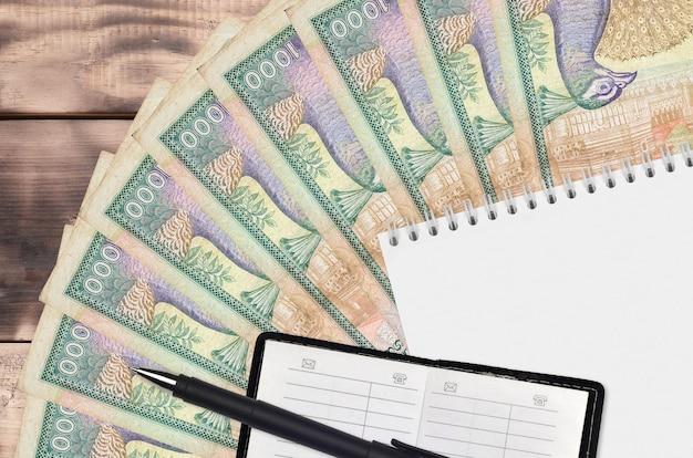 Wachlarz rachunków za 1000 rupii lankijskich, notatnik z książką kontaktową i czarnym długopisem.