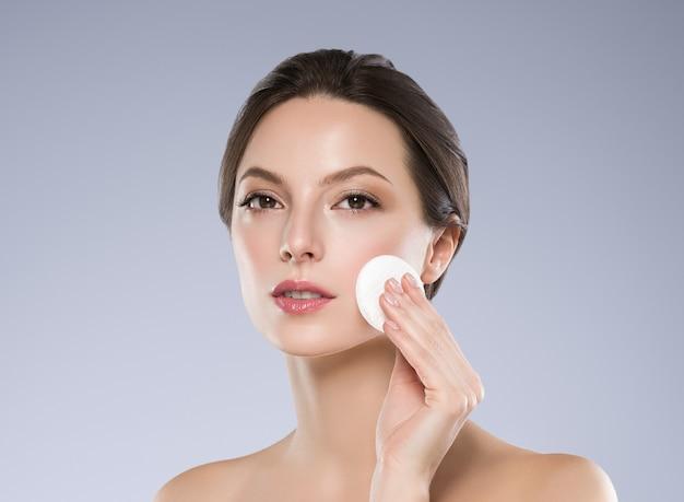 Wacik kosmetyczny twarz kobiety czysta skóra emoving makijaż. strzał studio. kolor tła.