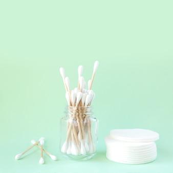 Waciki Bambusowe Z Organicznej Bawełny W Szklanym Słoju I Waciki Do Higieny Osobistej Na Jasnozielonej Powierzchni Premium Zdjęcia