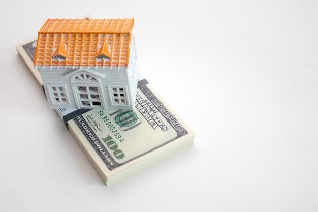Wad dolarów i model domu na białym tle.