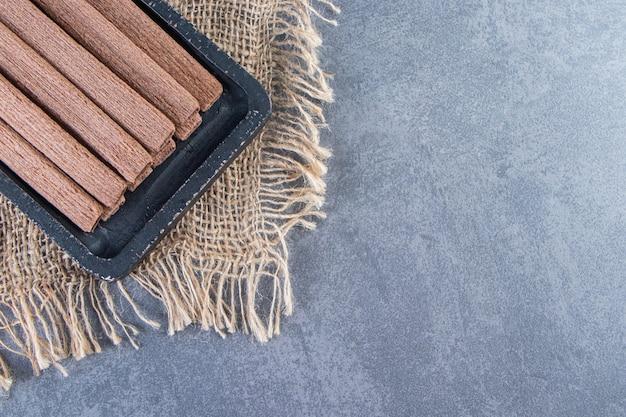 Wafel czekoladowy toczy się w desce na tekstury, na marmurowym tle.
