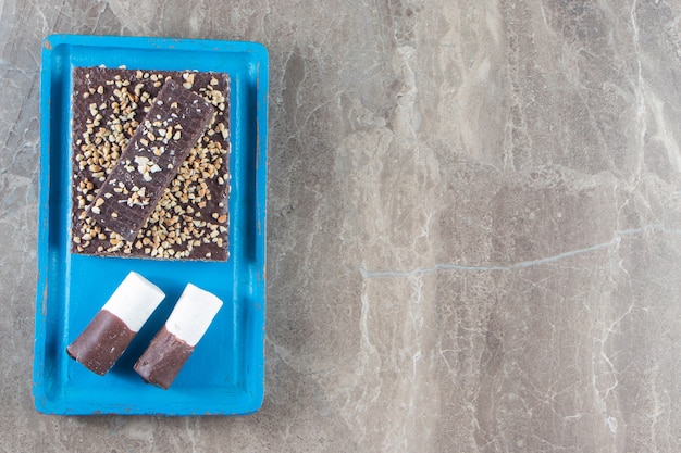 Wafel czekoladowy z orzechami i cukierkami na drewnianym talerzu na marmurze.