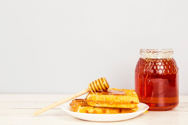 Wafel i miód w białym talerzu na zdrowe śniadanie