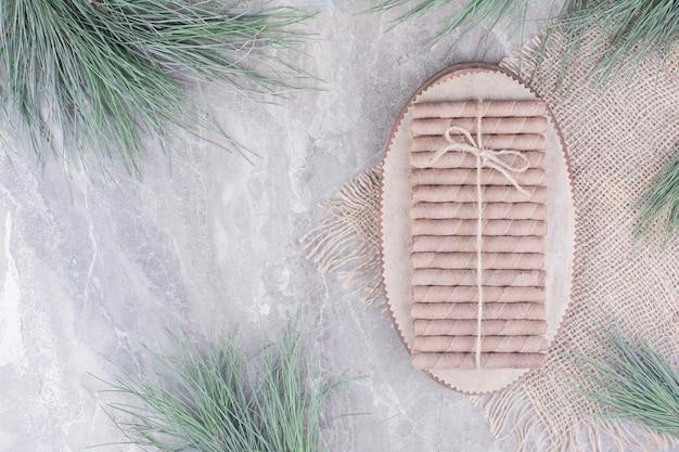 Wafel paluszki na drewnianym talerzu na rustykalnym.